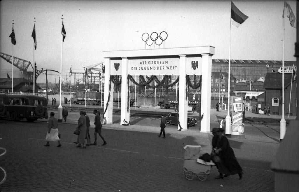 """Olympiator mit der Aufschrift Wir grüssen die Jugend der Welt""""vor der Kaisertreppe am Hauptbahnhof, 1936 / © Stadtarchiv Kiel"""
